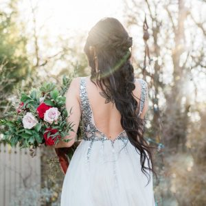 Bride wearing a white wedding dress holding a bouquet of roses on her wedding day with the sun setting behind her creating sun haze while she is being photographed by an Austin Texas wedding photographer.